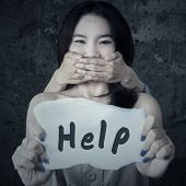 picture of kidnapped  - Scared teenage girl kidnapped by someone while holding a paper with a help text - JPG