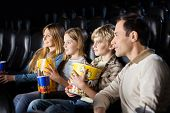 stock photo of movie theater  - Family having snacks while watching film in movie theater - JPG