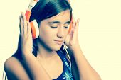 stock photo of puberty  - Instagram toned small teenage girl listening to music on her headphones - JPG