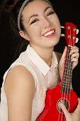 pic of ukulele  - Young teen girl holding red ukulele smiling - JPG