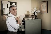 stock photo of 1950s style  - Cheerful smiling employee in 1950s style office searching for a file in the cabinet - JPG