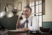 pic of 1950s  - Smiling handsome businessman on the phone working at desk 1950s vintage office - JPG