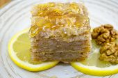 picture of baklava  - Juicy baklava on a plate decorated with lemon and walnuts ready to be eaten - JPG