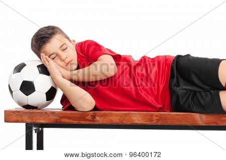 Kid in a football uniform sleeping on a wooden bench isolated on white background
