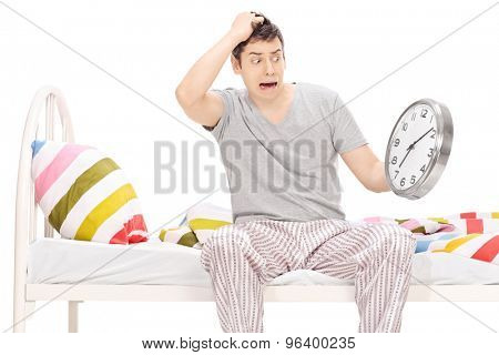 Shocked young man sitting on a bed in his pajamas and looking at the time isolated on white