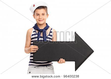 Little boy in sailor outfit holding a big black arrow pointing right isolated on white background