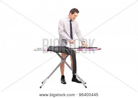 Cheerful young man ironing a pair of pants on an ironing board isolated on white background