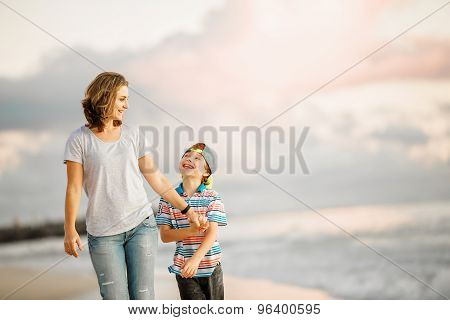 Young happy beautiful mother and her son having fun on the beach. Positive human emotions, feelings