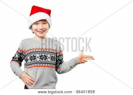 Portrait of a boy in christmas hat pointing at something with his fingers. Isolated