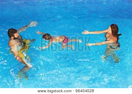Baby With Parents Diving Underwater In Outdoor Pool