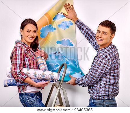 Happy family glues wallpaper on stairs at home.