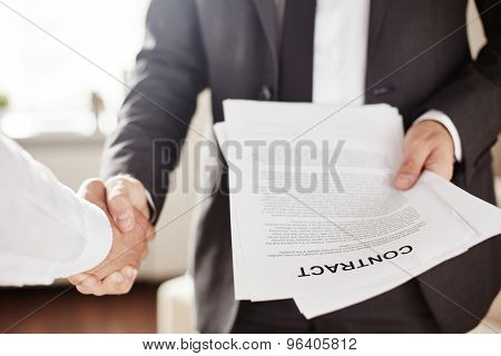Businessman with contract greeting his new partner