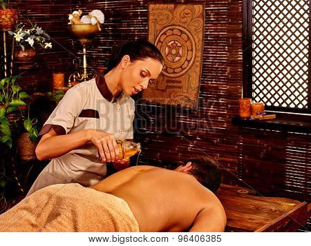 Man  having pouring oil Ayurveda spa treatment with window.