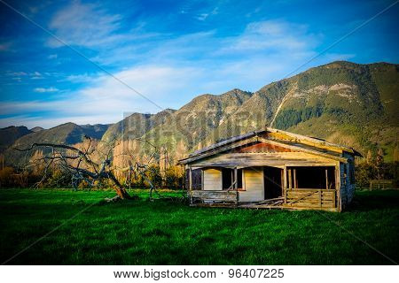 Old Abandoned Farmhouse With  An Old Dead Tree And View To The Mountain Range. Picture Taken At Suns