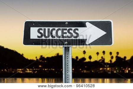 Success direction sign with sunset background