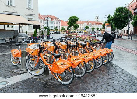Girl Takes Bicycle In Point Of Automatic Bicycle Rental Cyclocity In Old Town, Vilnius