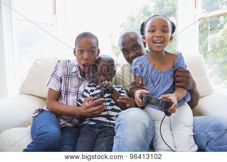 Happy smiling family playing video games together in the living room
