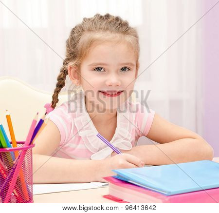 Cute Little Girl Is Writing At The Desk