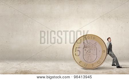 Young businessman rolling huge five euro coin