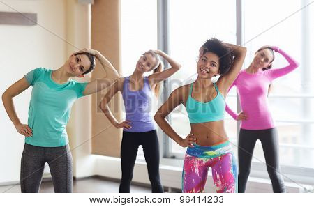 fitness, sport, training, gym and lifestyle concept - group of happy women  working out and stretchin poster