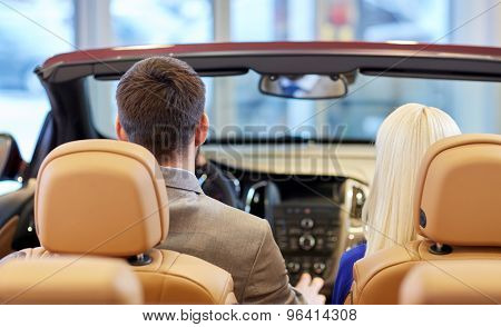 auto business, car sale, consumerism and people concept - close up of couple sitting in cabriolet car at auto show or salon from back
