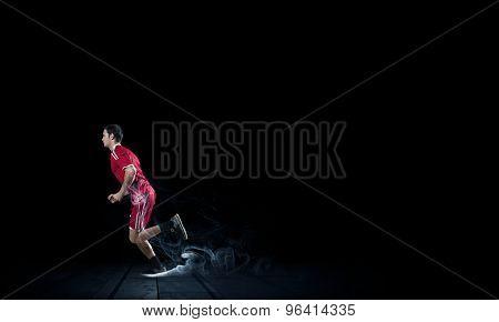 Running man in red sport wear on black background