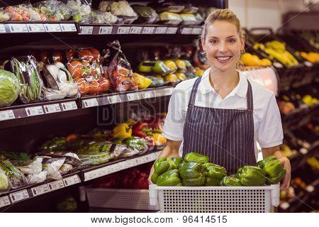 Portrait of a smiling blonde worker holding a vegetables in supermarket