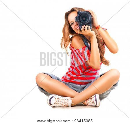 Photographer. Beauty Teenage Girl taking photo, sitting and Smiling. Beautiful Teen Girl with professional photo camera (unrecognizable). Isolated on a White Background. Teenager