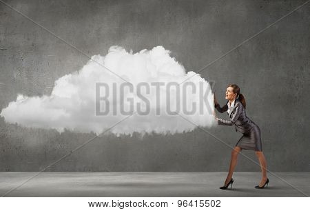 Attractive businesswoman pushing big cloud with effort