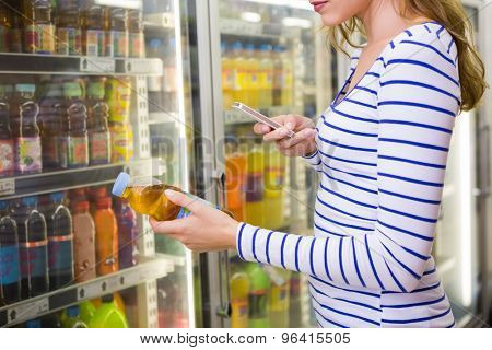 Pretty woman taking picture of bottle at supermarket