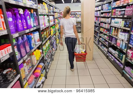 Woman walking with his trolley on aisle at the supermarket