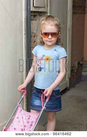 Lttle Girl In Sunglasses With A Toy Stroller