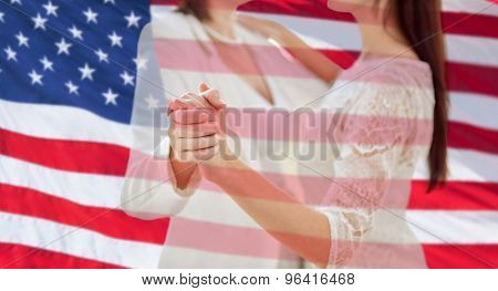 people, homosexuality, same-sex marriage and love concept - close up of happy married lesbian couple dancing over american flag background