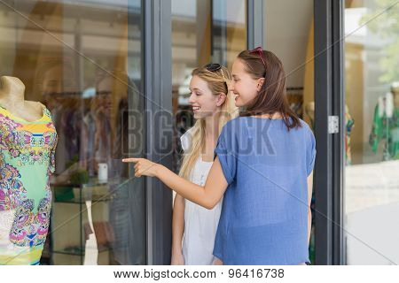 Friends finger pointing a dress through the window shop