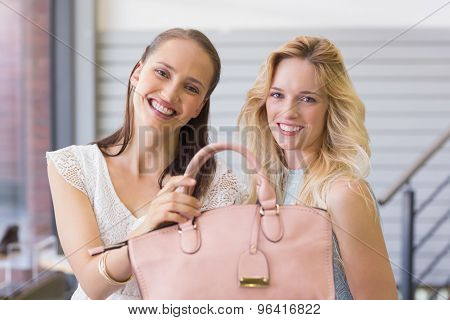Happy women smiling at camera and holding a handbag in shopping mall