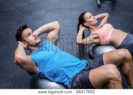 Muscular couple doing abdominal crunch on a bosu ball