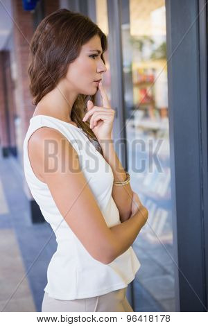 Concentrated woman looking at window at the shopping mall