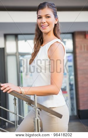 Portrait of smiling woman going upstairs at the shoppingmall