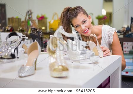 Portrait of smiling woman standing behind shoes at a shoe shop