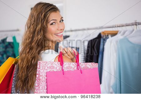 Portrait of smiling woman holding shopping bags and looking at camera at a boutique
