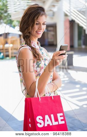 Smiling woman with sale shopping bags using smartphone at the shopping mall