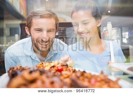 Young happy couple looking at cake in the cafe
