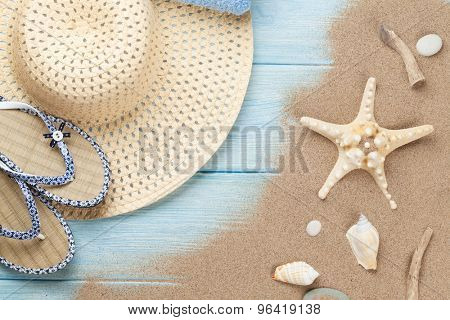 Travel and vacation items on wooden table with sea sand. Top view