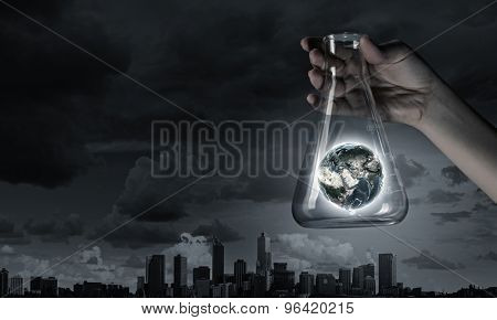 Hand holds flask with images on varied background. Elements of this image are furnished by NASA