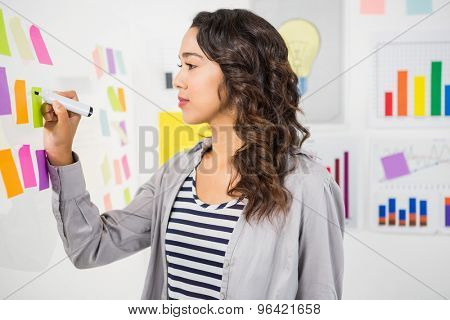 Young serious businesswoman writing on sticky notes on the wall in the office
