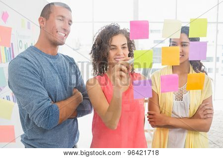 Smiling coworkers writing on sticky notes in the office