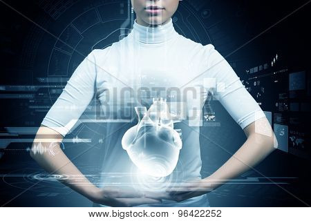 Futuristic woman holding human heart hologram in hands
