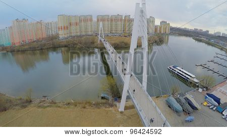 MOSCOW - APR 24, 2015: Lot of citizens walk by pedestrian bridge at spring cloudy day. Aerial view