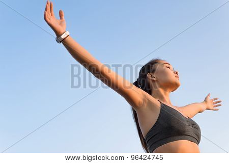 Asian woman raising arms to the sky.