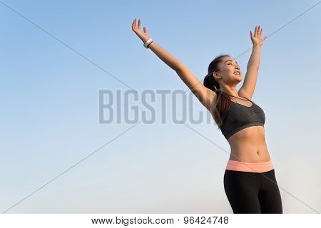 Happy asian woman raising arms to the sky.